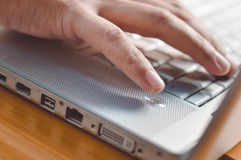 Closeup of fingers touching keyboard on wood table Stock Photography
