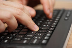 Closeup of fingers typing on computer keyboard Stock Photos