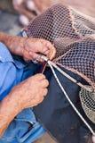 Closeup of fisherman repairing fishing net Stock Photo