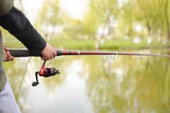 Closeup of fisherman`s hand holding rod with spinning Royalty Free Stock Photo