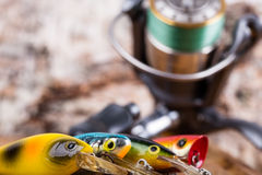 Closeup fishing baits wobblers with reel Royalty Free Stock Image
