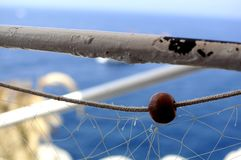 Closeup of a fishing net hang on a white pole on a ship at the seaside with a blue background royalty free stock photo