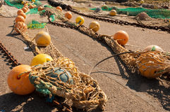 Closeup of a fishing nets with floats and chains Royalty Free Stock Image