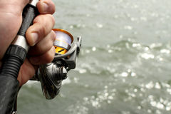 Closeup of fishing reel in hand Stock Photo