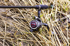 Closeup of fishing reel and rod on muddy spring ground. Closeup of fishing reel and rod leaning on muddy spring ground Royalty Free Stock Image