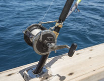 Closeup of fishing rod reel on side of boat Stock Images