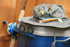 Closeup of fishing tackle box and hat. Fishing tackle box, hat and reel on wood Royalty Free Stock Photography