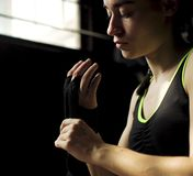 Closeup fit woman wrapping hands with bandage tape preparing for boxing training. Closeup fit young woman sitting on floor and wrapping hand with bandage tape royalty free stock photography