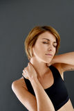 Closeup of fitness girl with pain in the neck Stock Photos