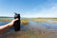 Closeup of fitness shaker bottle in the men's hand against the beautiful lake. Sports snack the fresh air. The concept of proper