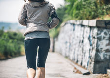 Closeup on fitness woman jogging in the city park. Closeup on fitness young woman jogging in the city park. rear view Stock Images