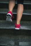 Closeup on fitness woman jogging in rainy city Royalty Free Stock Photo