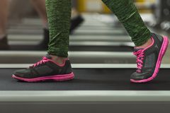 Closeup of fitness woman legs walking on treadmill at gym royalty free stock photos