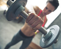 Closeup on fitness woman lifting dumbbell in loft gym Royalty Free Stock Images