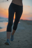 Closeup on fitness woman running on beach at dusk Stock Photos