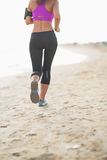 Closeup on fitness woman running on the beach . rear view Royalty Free Stock Photography