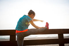 Closeup on fitness woman stretching on beach Stock Images