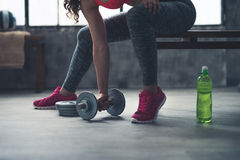 Closeup on fitness woman taking dumbbell from the floor in gym stock images