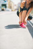 Closeup on fitness woman tying shoelaces outdoors Stock Photos