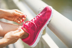 Closeup on fitness woman tying shoelaces outdoors Royalty Free Stock Photography