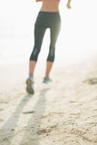 Closeup on fitness young woman running on beach Stock Photography