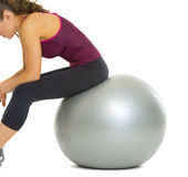 Closeup on fitness young woman sitting on fitness ball Stock Photos