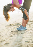 Closeup on fitness young woman stretching on beach Stock Photos