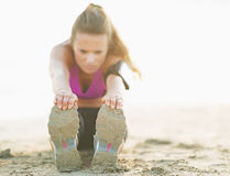 Closeup on fitness young woman stretching on beach Royalty Free Stock Photos
