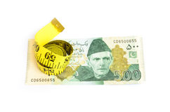 Closeup of five hundred rupee Pakistani currency bill and measure tape Royalty Free Stock Images