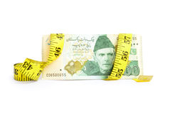 Closeup of five hundred rupee Pakistani currency bill wrapped in measure tape Royalty Free Stock Photo