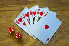 Closeup of Five Playing Cards - a Royal Flush - and two die royalty free stock images