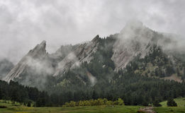Closeup of Flatiron mountains in Boulder, Colorado. Foggy weather and clouds shroud the Flatiron rock formations, part of the Rocky Mountain foothills just Royalty Free Stock Photos