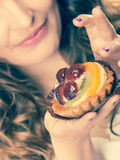 Closeup flirty woman eating fruit cake Stock Photography