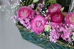 Closeup of flower arrangement in basket. With pink ranunculus and austeria with central ranunculus in focus and other flowers blurred Stock Image