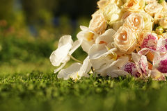 Closeup of flowers in a wedding bouquet, roses and orchids. Lying on the lawn in the setting sun Royalty Free Stock Photo