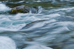 Closeup of flowing water with sea green and blue colors. Beautiful horizontal image of sea green flowing water on McKenzie river in Central Oregon. Soft textured Stock Photography