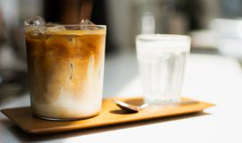 A glass of ice coffee on wooden tray. Closeup and focus to a glass of ice coffee on the wooden tray stock photo