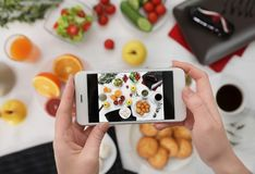 Closeup of food blogger photographing tasty breakfast with mobile phone royalty free stock photography