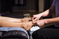 Thai foot massage in spa salon. Closeup Foot finger heel Thai massage to Asian tan woman on sofa in spa salon. Health care and Relax to heal pain concept royalty free stock photo