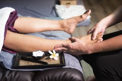 Closeup Foot heel Thai massage in spa. Closeup Foot heel Thai massage to Asian tan woman on sofa in spa salon. Health care and Relax to heal pain concept Stock Photography