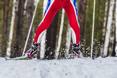 Closeup foot male skier sprays snow from under ski Stock Photos