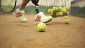 Closeup footage of female legs in sports sneakers and prosthesis on her leg picking up tennis balls from the tennis