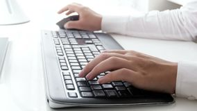 Closeup video of young businesswoman using computer mouse and typing on keyboard at office. Closeup footage of young businesswoman using computer mouse and stock footage