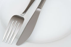 Closeup of fork and knife on a plate Royalty Free Stock Photo
