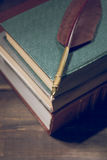 Closeup of fountain feather pen on stack of old books Stock Photo