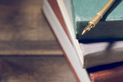 Closeup of fountain pen on stack of old books Stock Photo