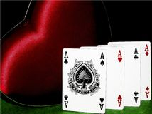 Closeup of four aces with big red heart on green table on black background, concept of love gambling, poker Stock Photos