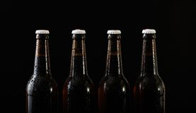 Closeup of four beer bottles isolated on black background. Closeup of four unopened beer bottles isolated on black background Stock Images