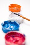 Closeup of four color paints in covers with paintb Royalty Free Stock Image