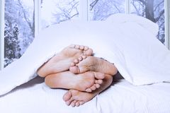 Closeup of four feet in a bed Stock Photo